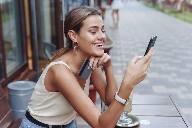 Une belle femme regarde son téléphone et tient une carte de crédit assise dans un café