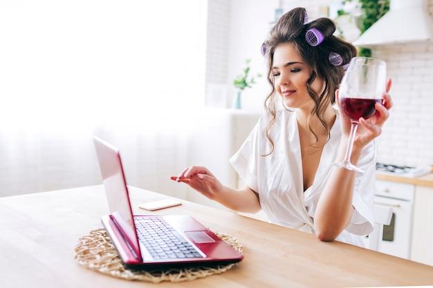Belle femme, regarder film, sur, ordinateur portable, et, boire, vin, dans, cuisine