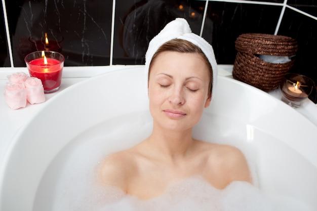 Belle femme relaxante dans un bain moussant