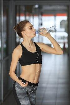 Belle femme de remise en forme debout avec haltère et eau potable