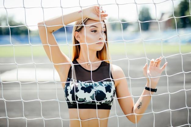 Belle femme de remise en forme sportswear posant près de la grille.