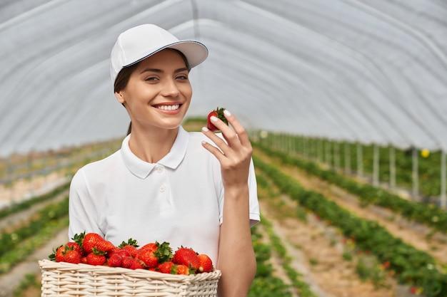 Belle femme reniflant et admirant la fraise