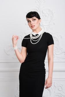 Belle femme rétro avec collier de perles à l'intérieur de luxe
