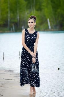 Belle femme rétro dans des vêtements vintage au bord du lac
