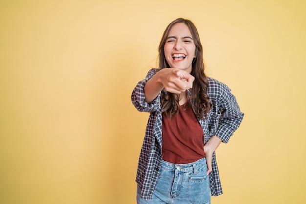 Belle femme riant avec un geste de la main pointant vers la caméra en se tenant debout avec fond