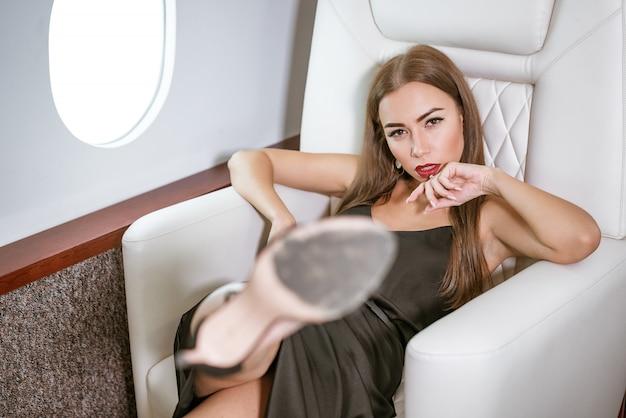 Belle femme riche dans un avion privé de première classe