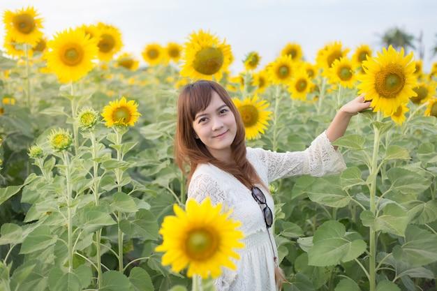 Belle femme en robe blanche sur un champ de tournesols d'été
