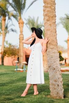 Belle femme en robe blanche et chapeau noir posant dans les environs d'un hôtel de luxe en vacances