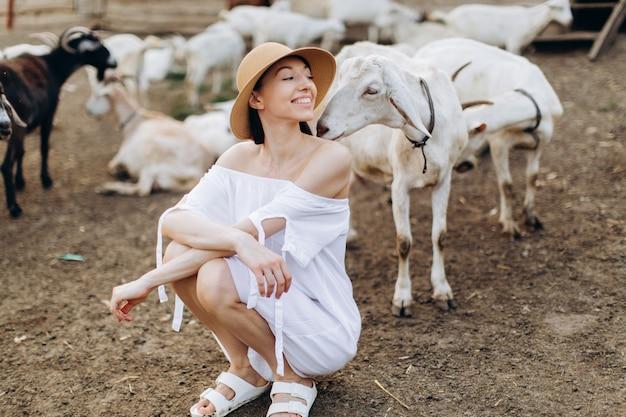 Belle femme et robe blanche et dans un chapeau beige parmi les chèvres dans une ferme écologique