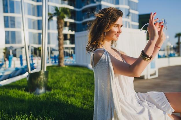 Belle femme en robe blanche à l'hôtel de villégiature d'été, portant des lunettes de soleil et des accessoires élégants, en riant, en vacances
