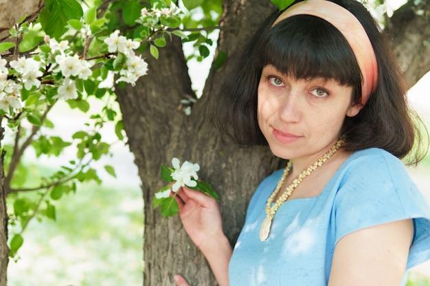 Belle femme en robe bleue sous un arbre en fleurs dans le jardin