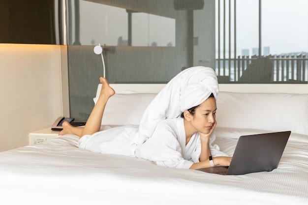 Belle femme en robe de chambre et serviette sur la tête allongée sur le lit et travaillant sur ordinateur portable.