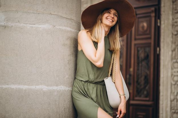 Belle femme en robe et chapeau debout par architecture