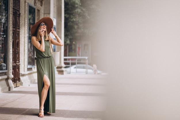 Belle femme en robe et chapeau parler au téléphone