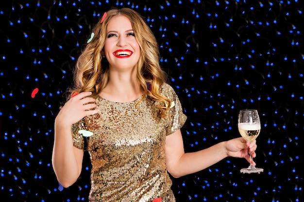 Belle femme en robe dorée avec coupe de champagne sur fond noir