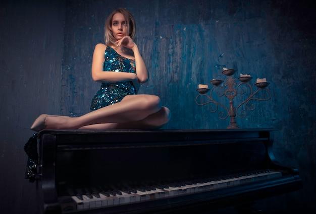 Belle femme avec une robe élégante fantaisie posant dans la salle de piano