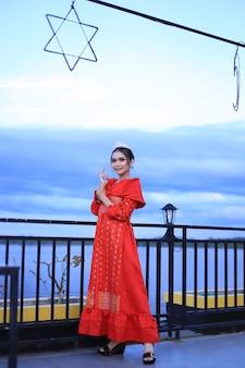 Belle femme en robe kebaya rouge