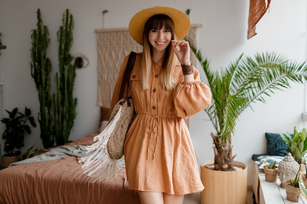 Belle femme en robe de lin et chapeau de paille posant dans un appartement de style bohème