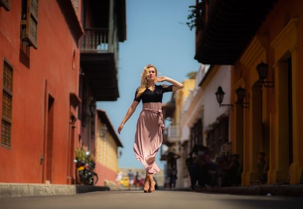 Belle femme avec une robe longue marchant seule dans les rues colorées de la ville coloniale fortifiée de carthagène. colombie.