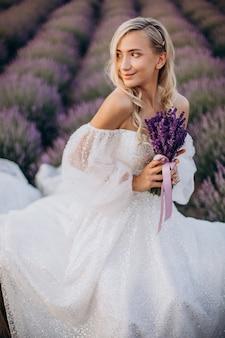 Belle femme en robe de mariée dans le champ de lavande