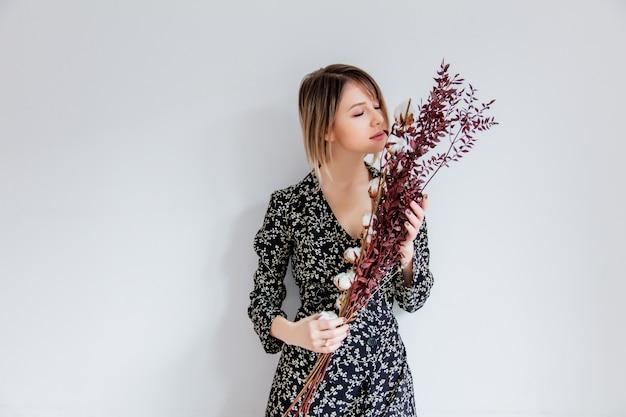 Belle femme en robe à la mode avec une branche de coton