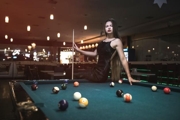 Belle femme en robe noire posant avec queue de billard