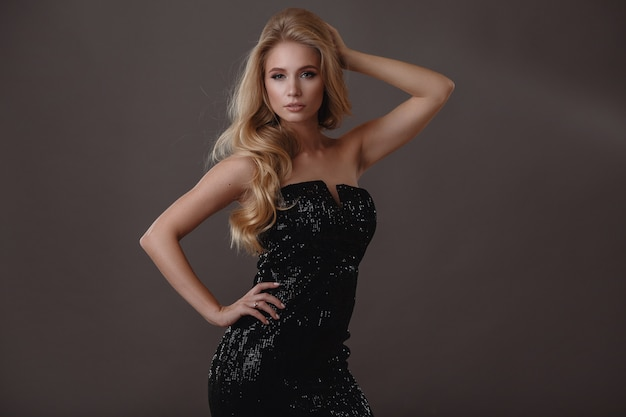 Belle femme en robe noire en studio