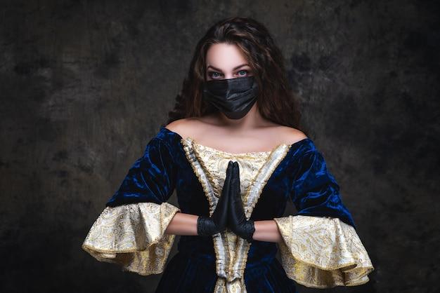 Belle femme en robe renaissance, masque facial et gants, coronavirus, concept de protection covid-19.