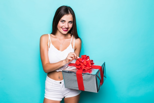 Belle femme en robe rose assise sur un gros cadeau, tenant une boîte-cadeau.