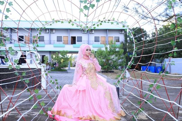 Belle femme en robe rose kebaya