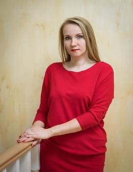Belle femme en robe rouge contre le mur.