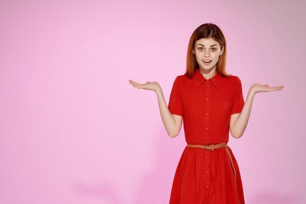 Belle femme en robe rouge fashion style élégant fond rose
