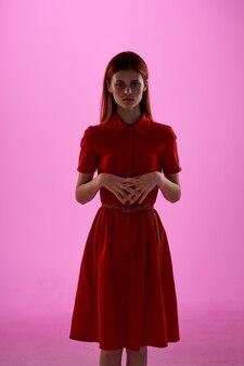 Belle femme en robe rouge gestes de la main fond rose de luxe. photo de haute qualité
