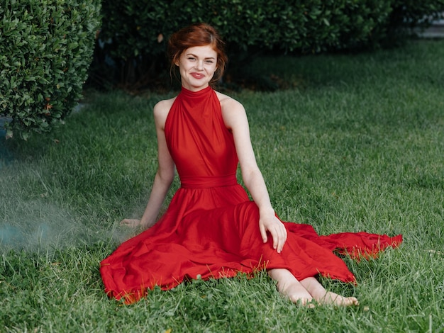 Belle femme robe rouge glamour nature herbe verte luxe. photo de haute qualité