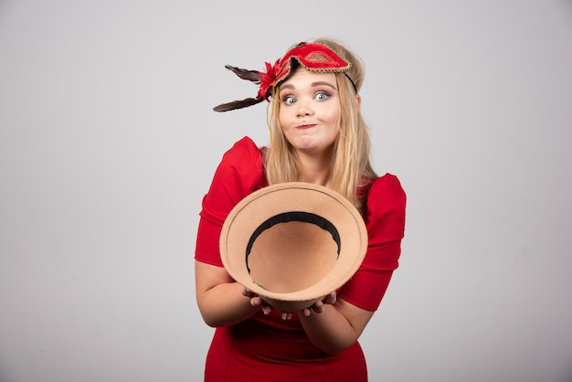 Belle femme en robe rouge offrant son chapeau.