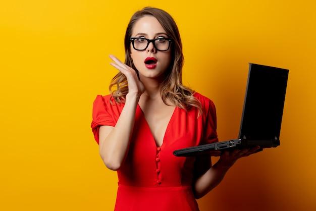Belle femme en robe rouge avec un ordinateur portable sur un mur jaune