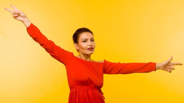 Belle femme en robe rouge pointant le doigt sur fond jaune