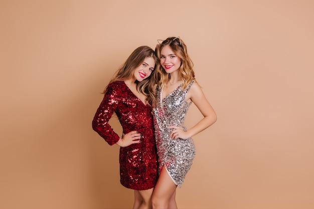 Belle femme en robe scintillante à manches longues posant avec le meilleur ami à la fête