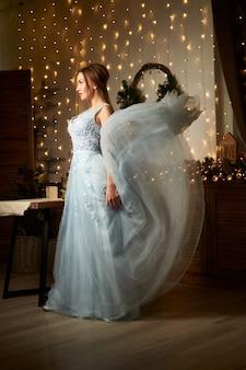 Belle femme en robe de soirée bleue concept de vacances d'hiver
