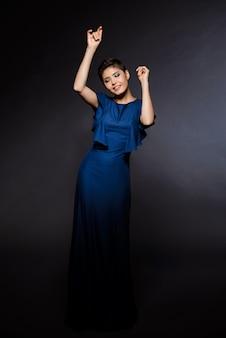 Belle femme en robe de soirée dansant, souriant