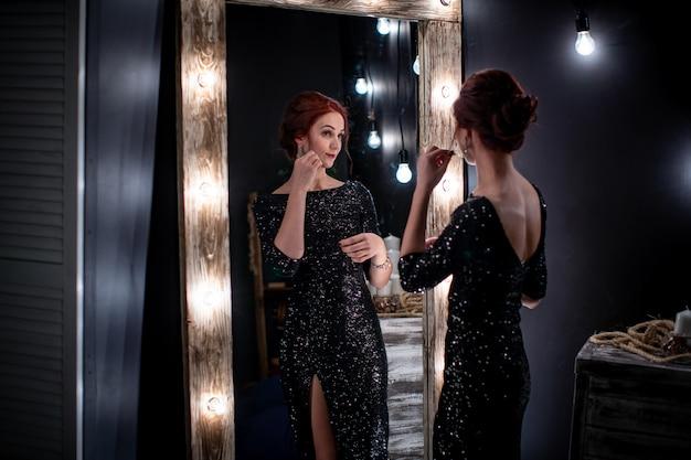 Belle femme en robe de soirée noire brillante se tient à côté d'un miroir haut foncé