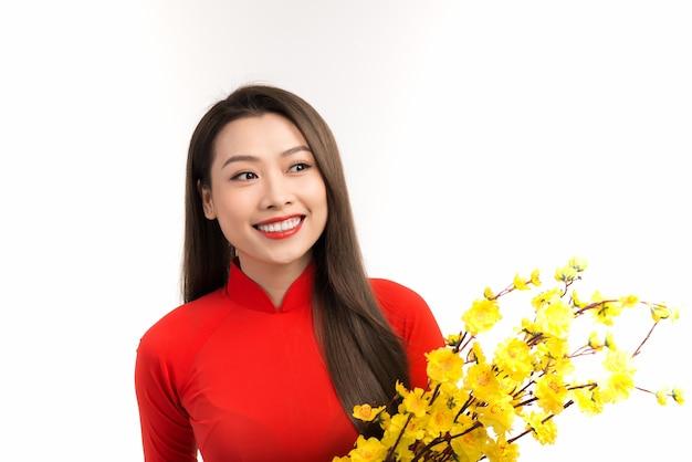 Belle femme avec la robe traditionnelle de culture du vietnam, tenant la fleur d'abricot au-dessus du blanc