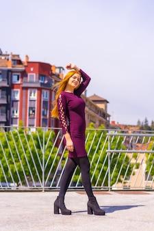 Belle femme en robe violette et bottes noires profitant d'un parc de la ville, posant en regardant la caméra