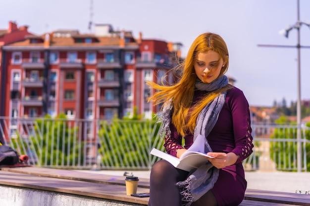 Belle femme en robe violette et écharpe lisant un livre dans un parc de la ville, imaginant et appréciant la lecture