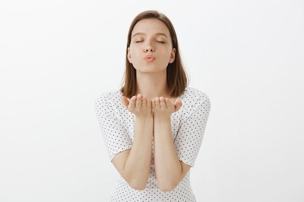 Belle femme romantique fermer les yeux et envoyer un baiser d'air