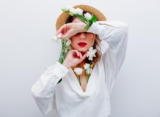 Belle femme avec des roses blanches dans les manches