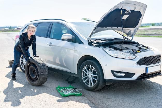 Belle femme avec roue de secours et voiture cassée