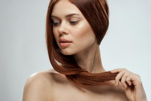Belle femme rousse aux cheveux raides. soin capillaire sain et brillant