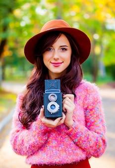 Belle femme rousse avec caméra en automne parc.
