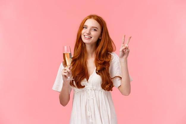Belle femme rousse caucasienne romantique en robe mignonne blanche, montrant le signe de la paix, salutation informelle d'un ami en fête, souriant tenant un verre de champagne, buvant comme pour célébrer, assister à l'événement
